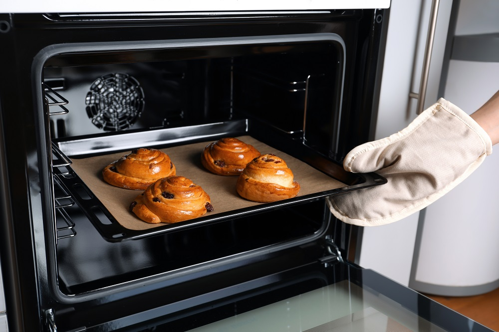 Woman taking baking sheet out of oven